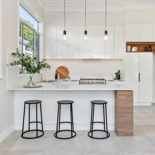 Inspiration for a contemporary u-shaped kitchen in Perth with a drop-in sink, flat-panel cabinets, white cabinets, white splashback, stainless steel appliances, a peninsula, grey floor and white benchtop.