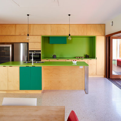 Example of a trendy galley beige floor open concept kitchen design in Adelaide with a double-bowl sink, flat-panel cabinets, beige cabinets, green backsplash, stainless steel appliances, an island and green countertops