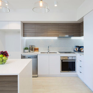 Contemporary l-shaped kitchen in Brisbane with a double-bowl sink, flat-panel cabinets, medium wood cabinets, white splashback, mosaic tile splashback, stainless steel appliances, light hardwood floors, an island, beige floor and white benchtop.