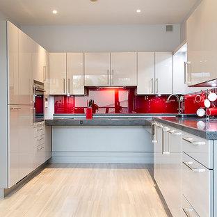 Offene, Kleine Moderne Küche ohne Insel in U-Form mit integriertem Waschbecken, flächenbündigen Schrankfronten, weißen Schränken, Mineralwerkstoff-Arbeitsplatte, Küchenrückwand in Rot, Glasrückwand, Küchengeräten aus Edelstahl, Laminat und beigem Boden in Buckinghamshire