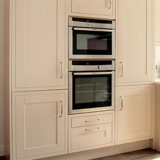 Idee per una grande cucina tradizionale con paraspruzzi rosa, elettrodomestici in acciaio inossidabile, penisola, lavello sottopiano, ante con riquadro incassato, ante beige, top in quarzite, paraspruzzi con piastrelle di vetro e pavimento con piastrelle in ceramica