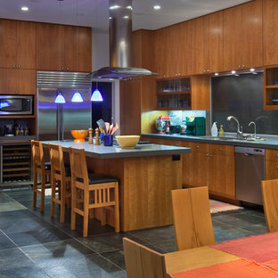 Inspiration for a large contemporary l-shaped eat-in kitchen in San Diego with flat-panel cabinets, medium wood cabinets, solid surface benchtops, grey splashback, slate splashback, stainless steel appliances, slate floors, with island and grey floor.