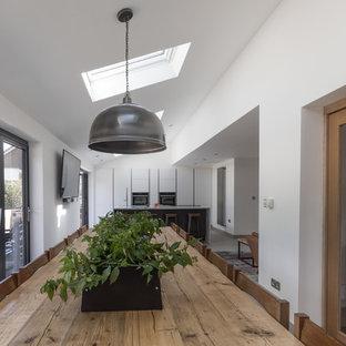 ハンプシャーの大きいコンテンポラリースタイルのおしゃれなキッチン (一体型シンク、フラットパネル扉のキャビネット、白いキャビネット、珪岩カウンター、パネルと同色の調理設備、マルチカラーのキッチンカウンター) の写真