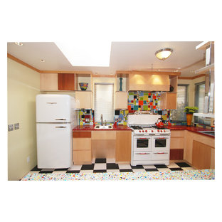 This is an example of a mid-sized modern u-shaped eat-in kitchen in San Francisco with a double-bowl sink, flat-panel cabinets, light wood cabinets, recycled glass benchtops, blue splashback, cement tile splashback, white appliances, linoleum floors and a peninsula.