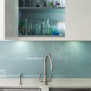 ロンドンの中くらいのコンテンポラリースタイルのおしゃれなキッチン (フラットパネル扉のキャビネット、中間色木目調キャビネット、再生ガラスカウンター、シルバーの調理設備) の写真
