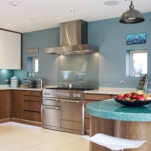 Foto de cocina comedor actual, de tamaño medio, con armarios con paneles lisos, puertas de armario de madera oscura, encimera de vidrio reciclado, electrodomésticos de acero inoxidable y península