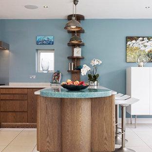 ロンドンの中サイズのコンテンポラリースタイルのおしゃれなキッチン (フラットパネル扉のキャビネット、中間色木目調キャビネット、再生ガラスカウンター、セラミックタイルの床) の写真