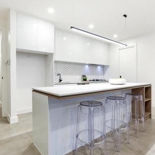 アデレードの広いコンテンポラリースタイルのおしゃれなキッチン (磁器タイルの床、ドロップインシンク、インセット扉のキャビネット、白いキャビネット、コンクリートカウンター、白いキッチンパネル、セラミックタイルのキッチンパネル、黒い調理設備、白い床、白いキッチンカウンター) の写真