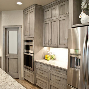 This is an example of a large shabby-chic style u-shaped kitchen in Other with recessed-panel cabinets, quartz benchtops, white splashback, stainless steel appliances and with island.