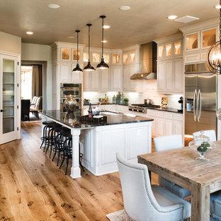Esempio di una cucina classica con lavello sottopiano, ante con bugna sagomata, ante bianche, paraspruzzi bianco, elettrodomestici in acciaio inossidabile, pavimento in legno massello medio e struttura in muratura