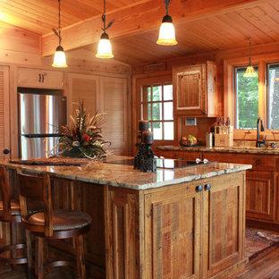 Diseño de cocina comedor lineal, rural, pequeña, con fregadero de doble seno, armarios con paneles con relieve, puertas de armario con efecto envejecido, encimera de granito, electrodomésticos de acero inoxidable, suelo de madera en tonos medios y una isla