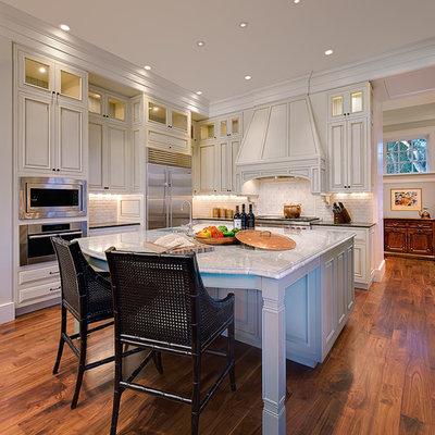 Kitchen - traditional kitchen idea in Charleston with white cabinets, white backsplash and limestone backsplash