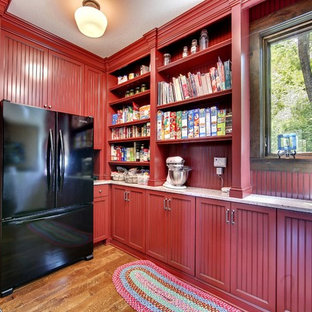 Rustic kitchen pantry ideas - Example of a mountain style medium tone wood floor and brown floor kitchen pantry design in Minneapolis with beaded inset cabinets, red cabinets, granite countertops, red backsplash, wood backsplash and black appliances