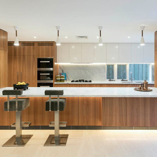 Inspiration for a contemporary galley eat-in kitchen in Sydney with an undermount sink, flat-panel cabinets, medium wood cabinets, white splashback, window splashback, panelled appliances, with island, white floor and white benchtop.
