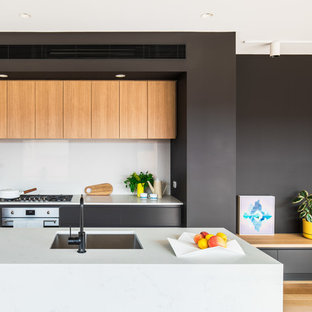 Design ideas for a mid-sized contemporary galley kitchen in Melbourne with an undermount sink, flat-panel cabinets, black cabinets, white splashback, stainless steel appliances, medium hardwood floors, with island, brown floor and white benchtop.