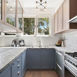 Small transitional u-shaped separate kitchen in Sydney with an undermount sink, shaker cabinets, blue cabinets, marble benchtops, white splashback, ceramic splashback, stainless steel appliances, dark hardwood floors, no island, brown floor and white benchtop.