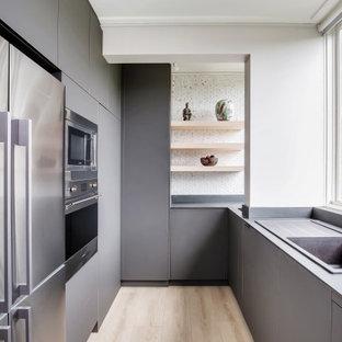Idéer för ett mellanstort modernt svart kök, med en enkel diskho, släta luckor, bruna skåp, kaklad bänkskiva, brunt stänkskydd, stänkskydd i keramik, rostfria vitvaror, ljust trägolv och brunt golv