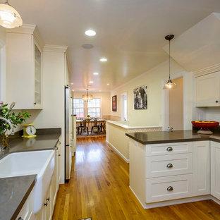 サンフランシスコの地中海スタイルのおしゃれなキッチン (エプロンフロントシンク、シェーカースタイル扉のキャビネット、黒いキャビネット、クオーツストーンカウンター、黒いキッチンパネル、石スラブのキッチンパネル、シルバーの調理設備の) の写真