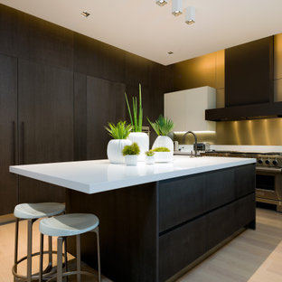 Große Moderne Küche in U-Form mit flächenbündigen Schrankfronten, dunklen Holzschränken, Küchenrückwand in Gelb, Elektrogeräten mit Frontblende, Kücheninsel, beigem Boden und weißer Arbeitsplatte in Dallas