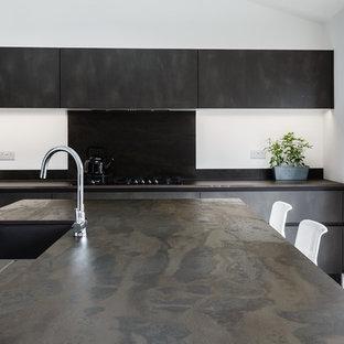 エセックスの中サイズのコンテンポラリースタイルのおしゃれなキッチン (一体型シンク、フラットパネル扉のキャビネット、グレーのキャビネット、人工大理石カウンター、グレーのキッチンパネル、パネルと同色の調理設備、クッションフロア、マルチカラーの床、グレーのキッチンカウンター) の写真