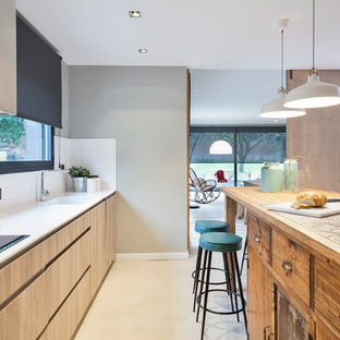 This is an example of a large contemporary galley separate kitchen in Barcelona with an integrated sink, flat-panel cabinets, light wood cabinets, tile benchtops, white splashback, stainless steel appliances, concrete floors and with island.