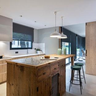 バルセロナの大きいコンテンポラリースタイルのおしゃれなキッチン (一体型シンク、フラットパネル扉のキャビネット、淡色木目調キャビネット、シルバーの調理設備の、コンクリートの床、タイルカウンター、白いキッチンパネル) の写真