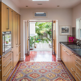 Example of a mid-sized trendy galley porcelain floor enclosed kitchen design in Los Angeles with an undermount sink, flat-panel cabinets, medium tone wood cabinets, metallic backsplash, solid surface countertops, stone tile backsplash, stainless steel appliances and no island