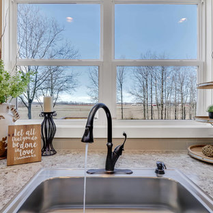 Large country u-shaped medium tone wood floor and brown floor open concept kitchen photo in Grand Rapids with a drop-in sink, shaker cabinets, white cabinets, beige backsplash, porcelain backsplash, stainless steel appliances, an island and beige countertops