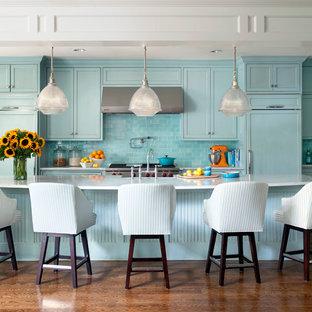 リトルロックのトランジショナルスタイルのおしゃれなキッチン (シェーカースタイル扉のキャビネット、青いキャビネット、大理石カウンター、青いキッチンパネル、サブウェイタイルのキッチンパネル、シルバーの調理設備の、濃色無垢フローリング) の写真