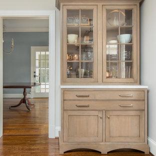 Große Klassische Wohnküche in L-Form mit Landhausspüle, Schrankfronten im Shaker-Stil, Granit-Arbeitsplatte, Küchengeräten aus Edelstahl, braunem Holzboden, Kücheninsel, schwarzer Arbeitsplatte, beigen Schränken, Küchenrückwand in Beige, Rückwand aus Stein und braunem Boden in New Orleans