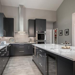 セントルイスの広いモダンスタイルのおしゃれなキッチン (エプロンフロントシンク、フラットパネル扉のキャビネット、グレーのキャビネット、クオーツストーンカウンター、グレーのキッチンパネル、ガラス板のキッチンパネル、シルバーの調理設備、無垢フローリング、グレーの床、白いキッチンカウンター) の写真