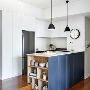 Design ideas for a mid-sized contemporary u-shaped open plan kitchen in Sydney with an undermount sink, shaker cabinets, blue cabinets, quartz benchtops, white splashback, stainless steel appliances, medium hardwood floors, a peninsula, brown floor and white benchtop.