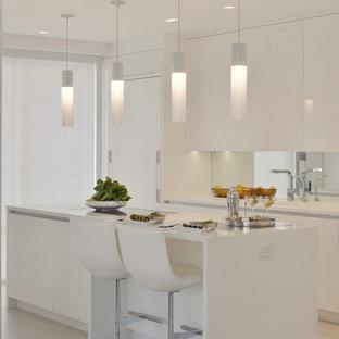 Ejemplo de cocina en L, contemporánea, pequeña, cerrada, con fregadero integrado, armarios con paneles lisos, puertas de armario blancas, encimera de acrílico, salpicadero con efecto espejo, electrodomésticos blancos, suelo de baldosas de porcelana, una isla y suelo beige