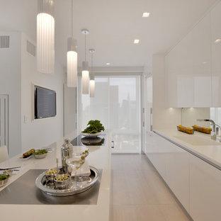 Foto de cocina en L, contemporánea, pequeña, cerrada, con fregadero integrado, armarios con paneles lisos, puertas de armario blancas, encimera de acrílico, salpicadero con efecto espejo, electrodomésticos blancos, suelo de baldosas de porcelana, una isla y suelo beige