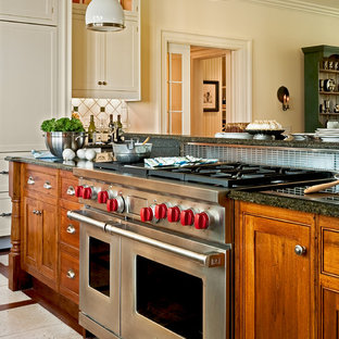 Elegant eat-in kitchen photo in New York with stainless steel appliances, recessed-panel cabinets, medium tone wood cabinets, a drop-in sink, granite countertops, multicolored backsplash and ceramic backsplash