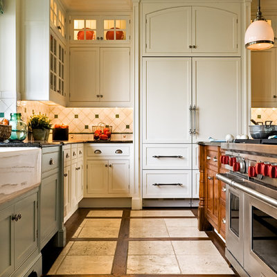 Eat-in kitchen - traditional multicolored floor eat-in kitchen idea in New York with a farmhouse sink, recessed-panel cabinets, white cabinets, granite countertops, paneled appliances, multicolored backsplash and ceramic backsplash