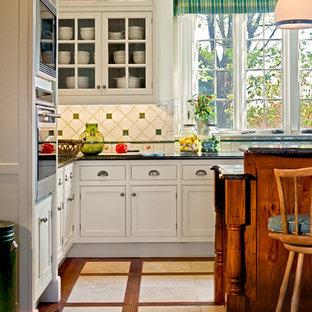 Klassische Wohnküche mit Schrankfronten mit vertiefter Füllung, weißen Schränken, Granit-Arbeitsplatte, Einbauwaschbecken, bunter Rückwand, Rückwand aus Keramikfliesen, Küchengeräten aus Edelstahl, buntem Boden und Mauersteinen in New York