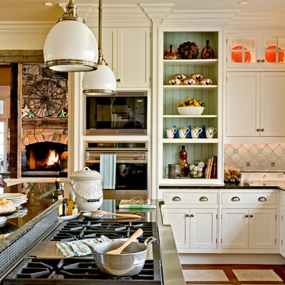 Example of a classic eat-in kitchen design in New York with recessed-panel cabinets, stainless steel appliances, white cabinets, granite countertops, multicolored backsplash, a farmhouse sink and ceramic backsplash