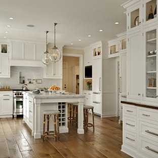 Inspiration for a large timeless u-shaped medium tone wood floor enclosed kitchen remodel in New York with marble countertops, shaker cabinets, white cabinets, paneled appliances, white backsplash, stone slab backsplash and an island