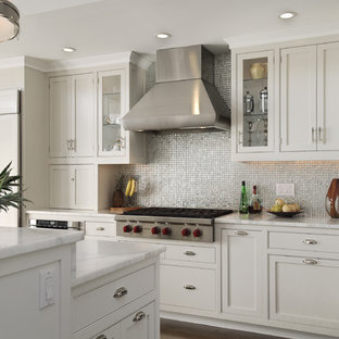 Eat-in kitchen - farmhouse eat-in kitchen idea in New York with mosaic tile backsplash, stainless steel appliances, white cabinets, marble countertops, metallic backsplash, a drop-in sink and beaded inset cabinets