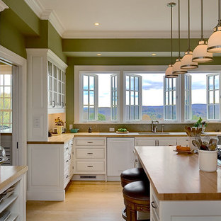 Traditional eat-in kitchen ideas - Elegant eat-in kitchen photo in New York with glass-front cabinets, white cabinets, wood countertops, white appliances, an undermount sink and white backsplash
