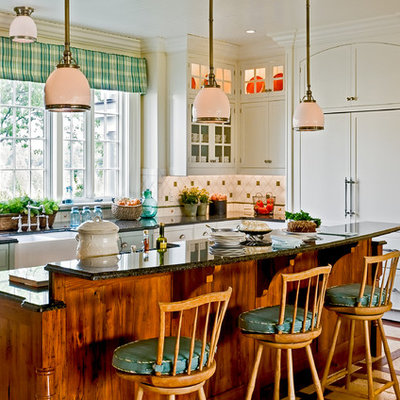 Inspiration for a timeless eat-in kitchen remodel in New York with paneled appliances, a farmhouse sink, white cabinets, granite countertops, multicolored backsplash, recessed-panel cabinets and ceramic backsplash