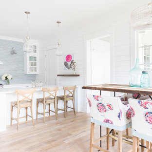 Farmhouse eat-in kitchen photos - Example of a country light wood floor and beige floor eat-in kitchen design in Nashville with glass-front cabinets, white cabinets, subway tile backsplash, stainless steel appliances, a peninsula and blue backsplash