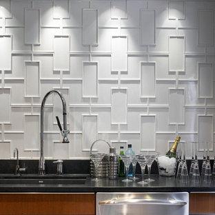 Foto de cocina comedor en L, minimalista, con electrodomésticos de acero inoxidable, fregadero de un seno, armarios con paneles lisos, puertas de armario de madera oscura, encimera de granito, salpicadero blanco y salpicadero de azulejos de cerámica