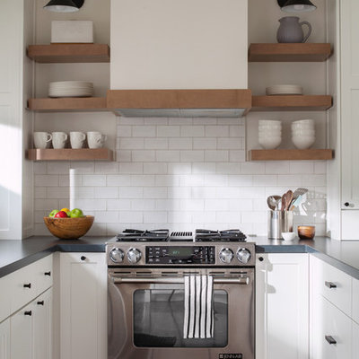 Example of a beach style u-shaped dark wood floor kitchen design in San Francisco with shaker cabinets, white cabinets, white backsplash, subway tile backsplash, stainless steel appliances and gray countertops