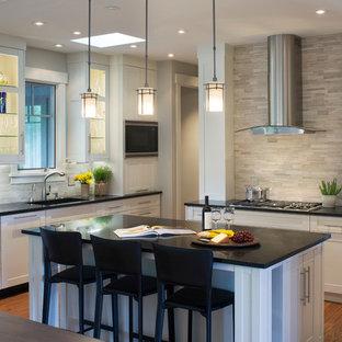 Klassische Küche mit Waschbecken, Schrankfronten im Shaker-Stil, weißen Schränken, Granit-Arbeitsplatte, Küchenrückwand in Grau, Küchengeräten aus Edelstahl, braunem Holzboden, Kücheninsel und Kalk-Rückwand in Sonstige