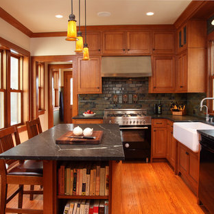Craftsman enclosed kitchen inspiration - Example of an arts and crafts l-shaped enclosed kitchen design in Minneapolis with a farmhouse sink, recessed-panel cabinets, medium tone wood cabinets, soapstone countertops and stainless steel appliances