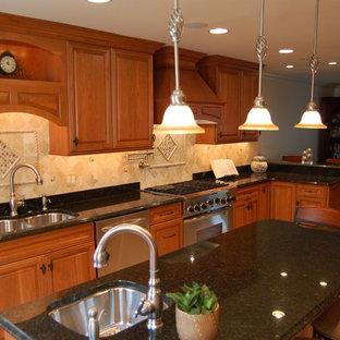 ボルチモアの大きいトラディショナルスタイルのおしゃれなキッチン (ダブルシンク、レイズドパネル扉のキャビネット、中間色木目調キャビネット、御影石カウンター、ベージュキッチンパネル、トラバーチンのキッチンパネル、シルバーの調理設備、トラバーチンの床、ベージュの床、黒いキッチンカウンター) の写真