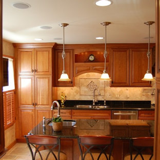 Large traditional galley eat-in kitchen in Baltimore with a double-bowl sink, raised-panel cabinets, medium wood cabinets, granite benchtops, beige splashback, travertine splashback, stainless steel appliances, travertine floors, with island, beige floor and black benchtop.