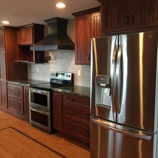 ブリッジポートの広いカントリー風おしゃれなキッチン (エプロンフロントシンク、インセット扉のキャビネット、濃色木目調キャビネット、御影石カウンター、白いキッチンパネル、トラバーチンのキッチンパネル、シルバーの調理設備、クッションフロア、茶色い床、マルチカラーのキッチンカウンター) の写真
